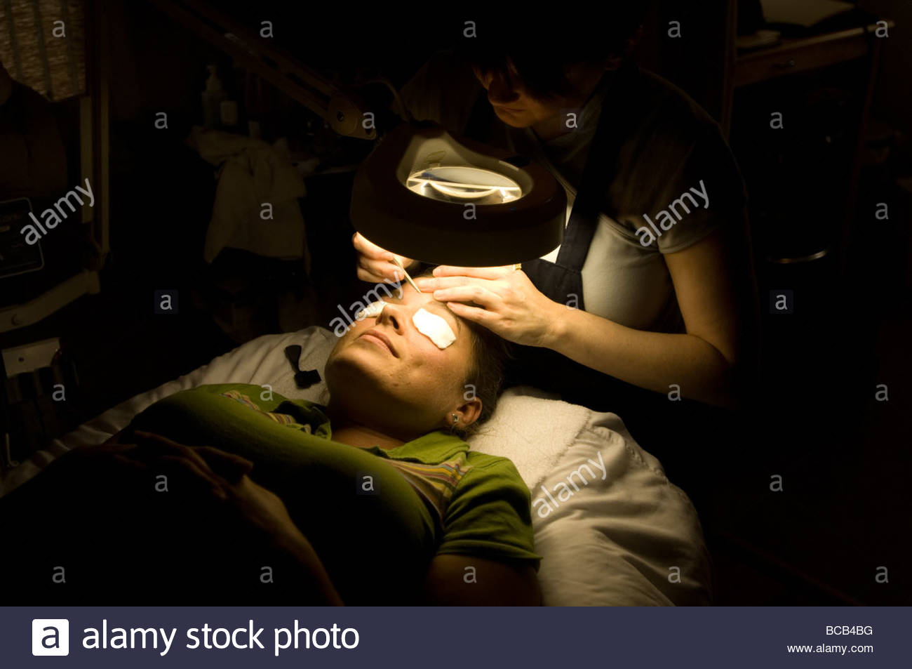 A woman gets her eye brows plucked at a Nebraska spa. - Stock Image