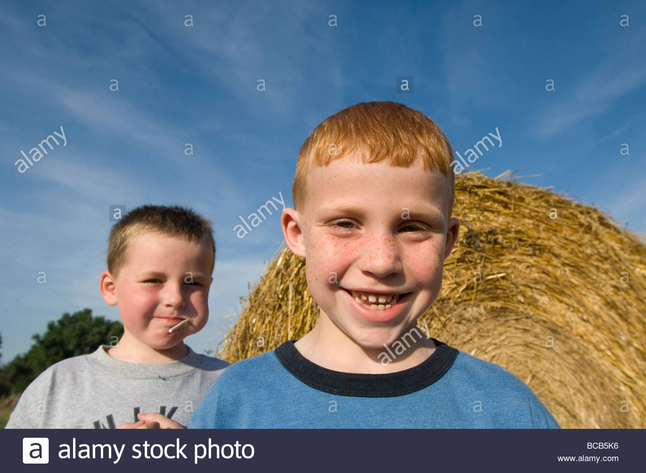 Two young kids by a haybale in Greenleaf, Kansas. - Stock Image