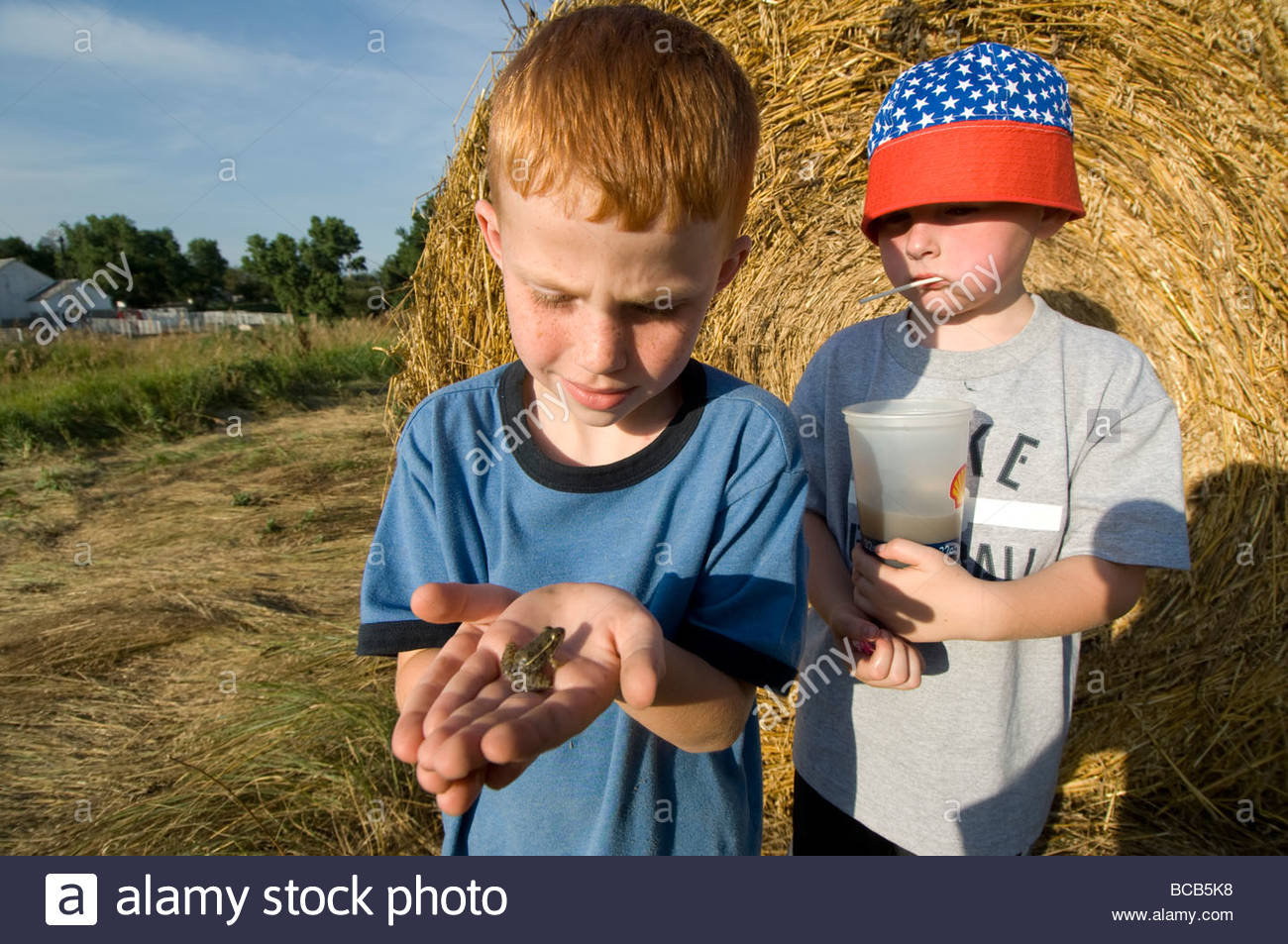 Two young kids look at a plains leopard frog (Rana blairi). - Stock Image