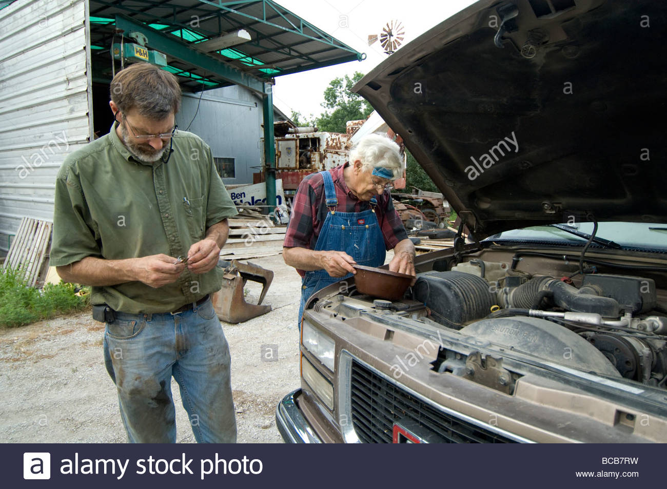 Two men repair a truck engine at a farm in Nebraska. - Stock Image