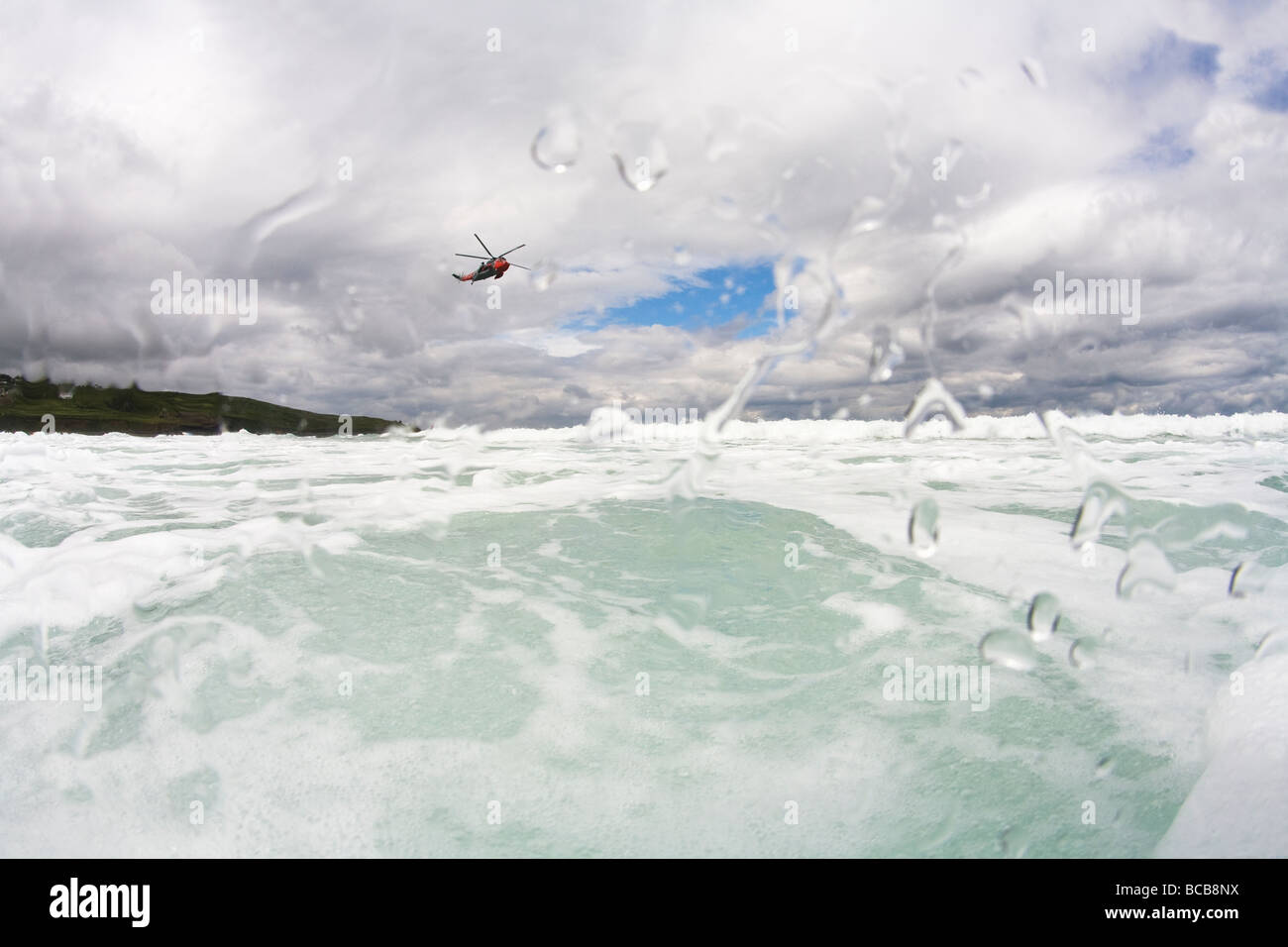 Royal Navy Search and Rescue Helicopter flies over waves off Porthmeor beach in summer St Ives Cornwall England - Stock Image