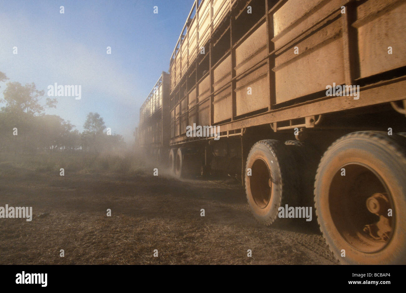 The wheels of a longhall road train churn up the dust in the outback. Stock Photo