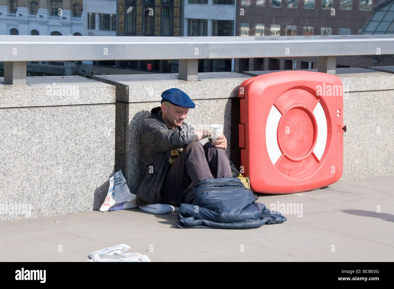 A homeless person on London Bridge in London. - Stock Image