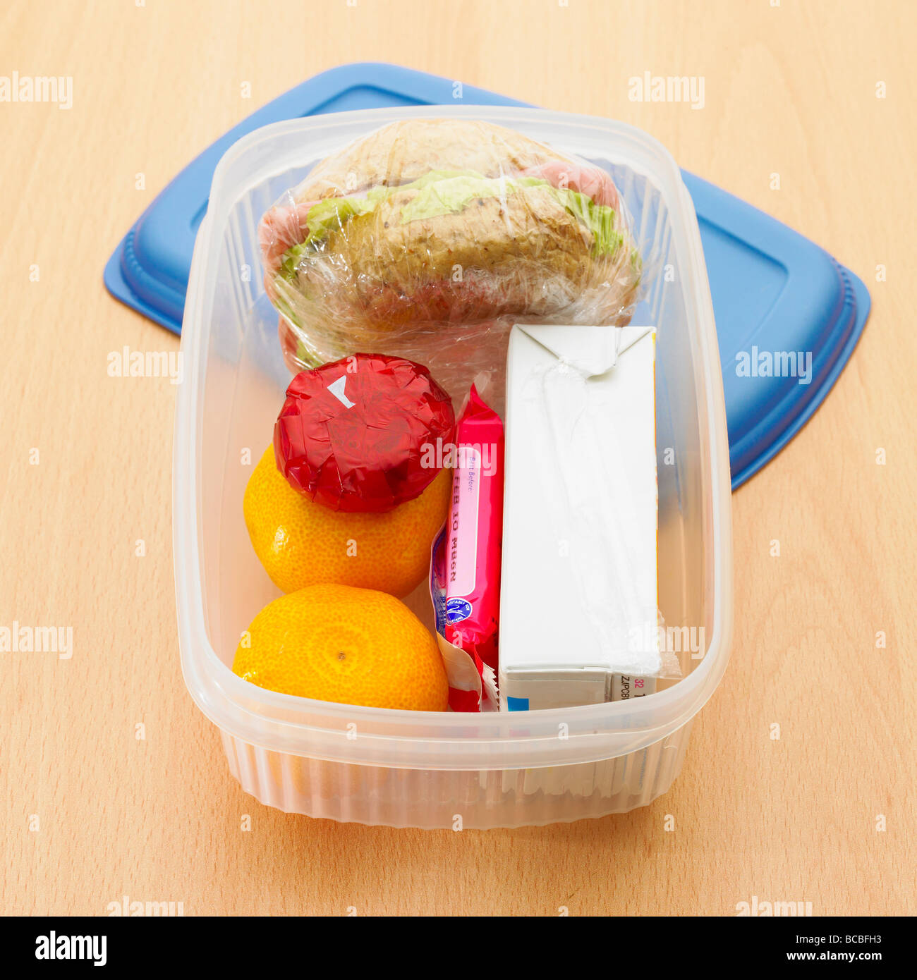 Healthy lunch box with wholemeal roll, satsumas, mini light cheese, orange juice and biscuit. - Stock Image