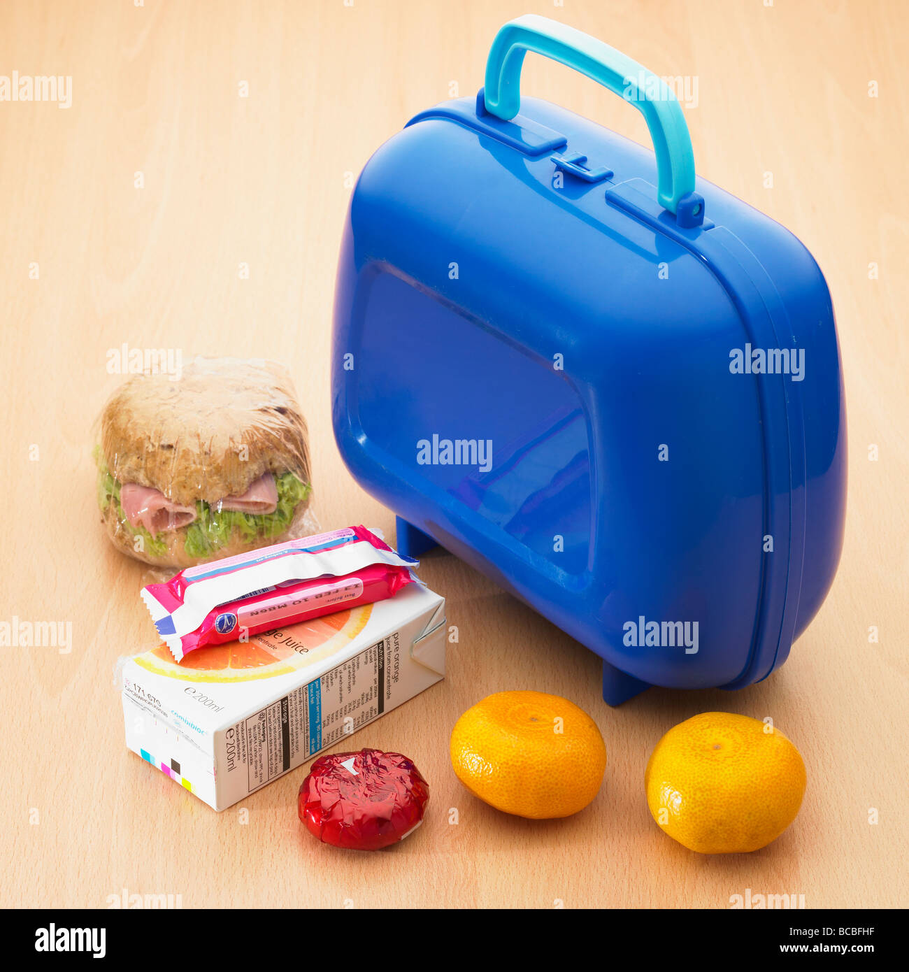 Healthy childrens school lunch box with wholemeal roll,satsumas,light cheese, orange juice and biscuit. - Stock Image