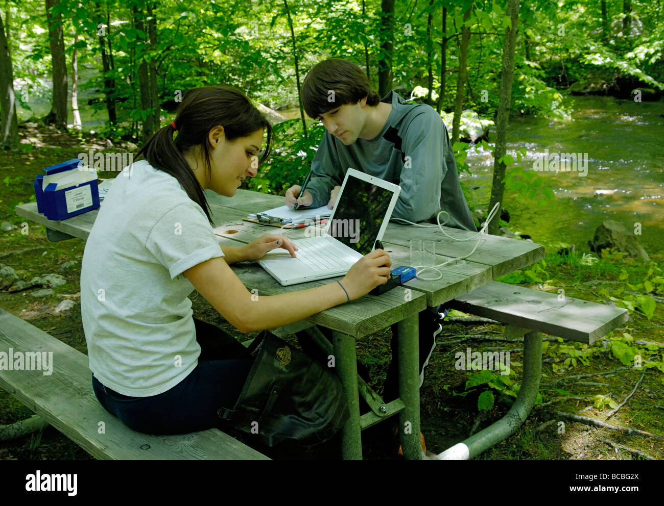 Two teens using a laptop interfaced sensor to measure the water quality of a stream - Stock Image