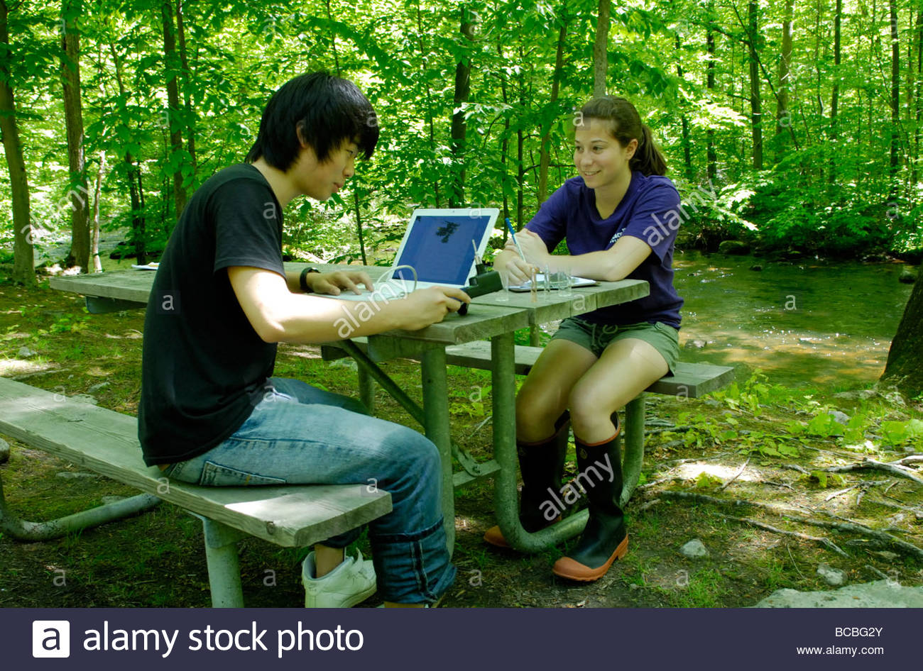 Two teens using a laptop interfaced sensor to measure the water quality of a stream Stock Photo