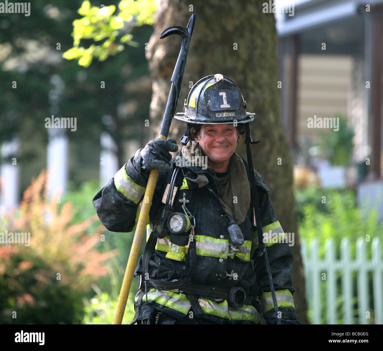 A female firefighter smiles with dirty face after battling a blaze in New Haven Connecticut USA - Stock Image