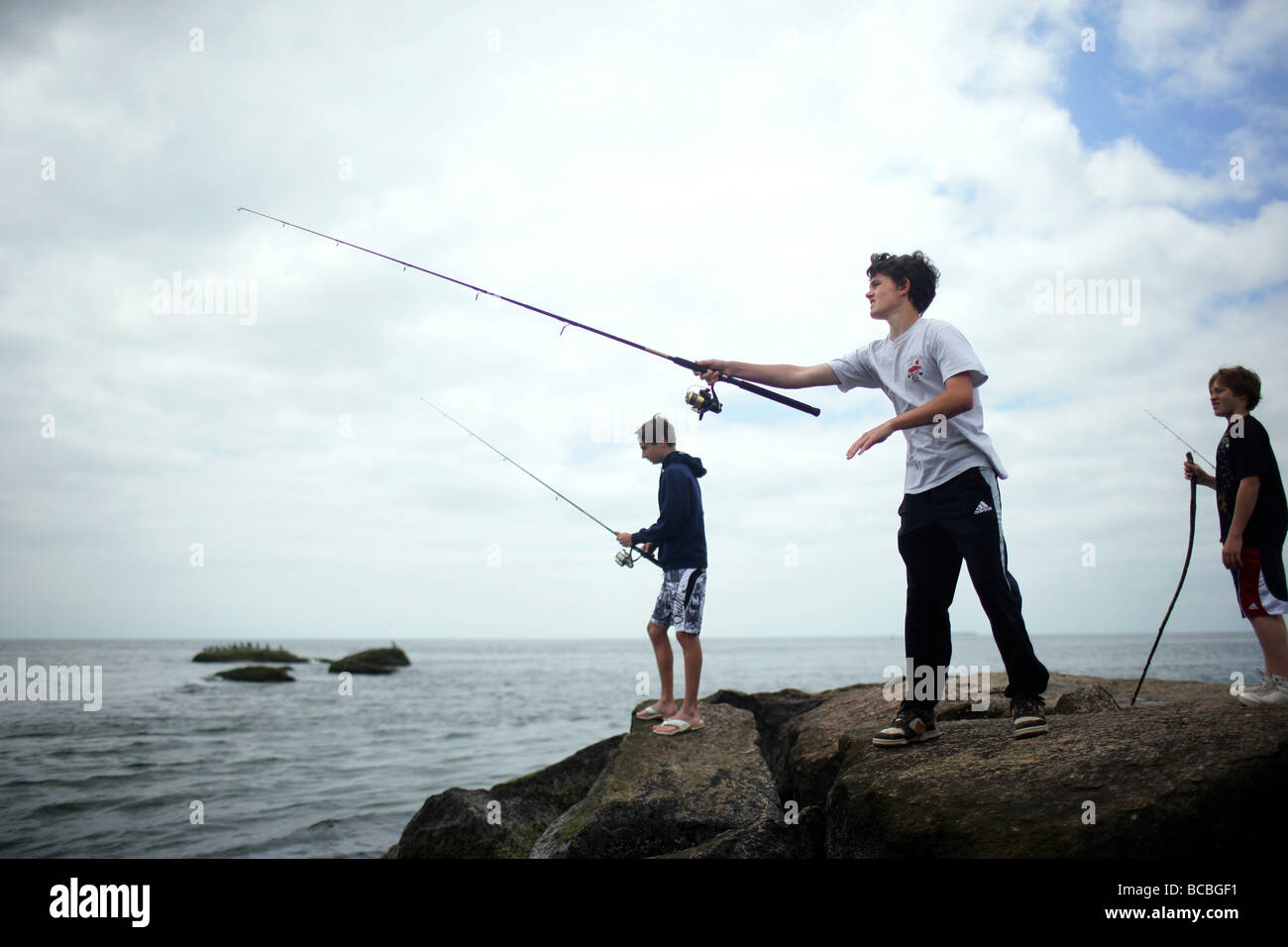 Youths fish off of a Jetty in Madison Connecticut USA - Stock Image