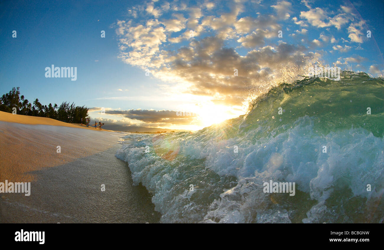 Wave crashing on beach - Stock Image