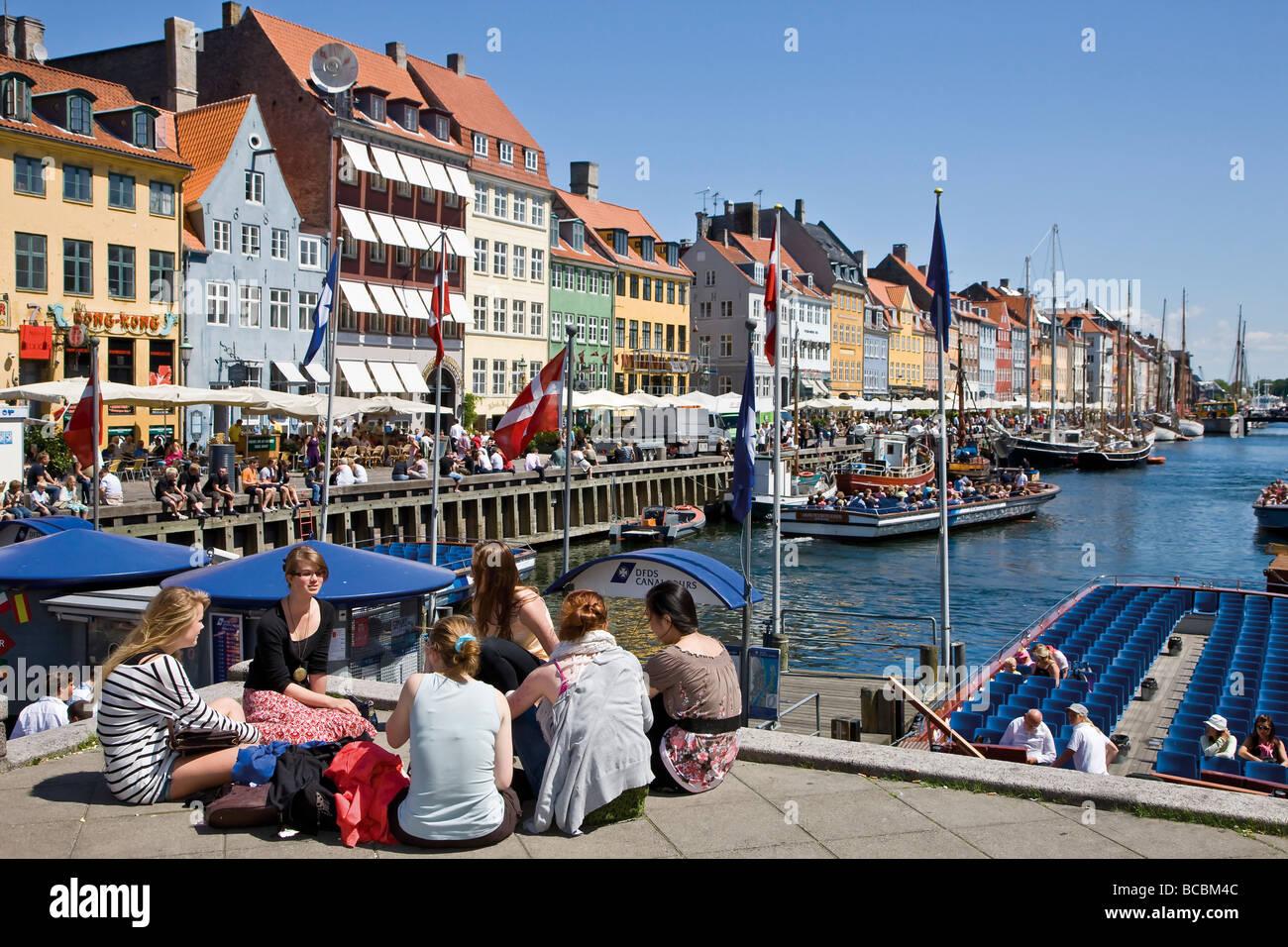 Tourists relaxing in Nyhavn Copenhagen - Stock Image