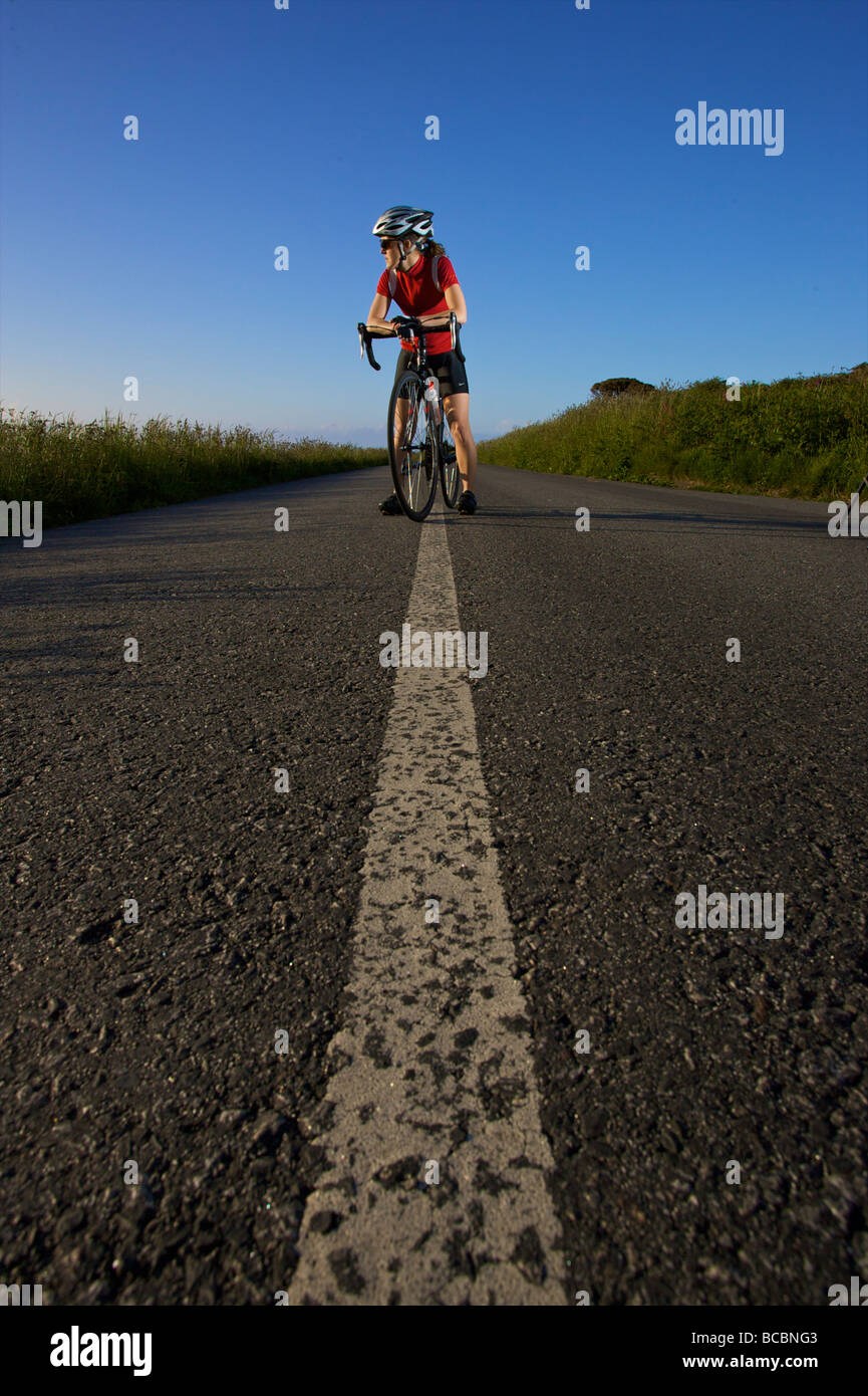 A female road cyclist on the Cornwall coastal road - Stock Image