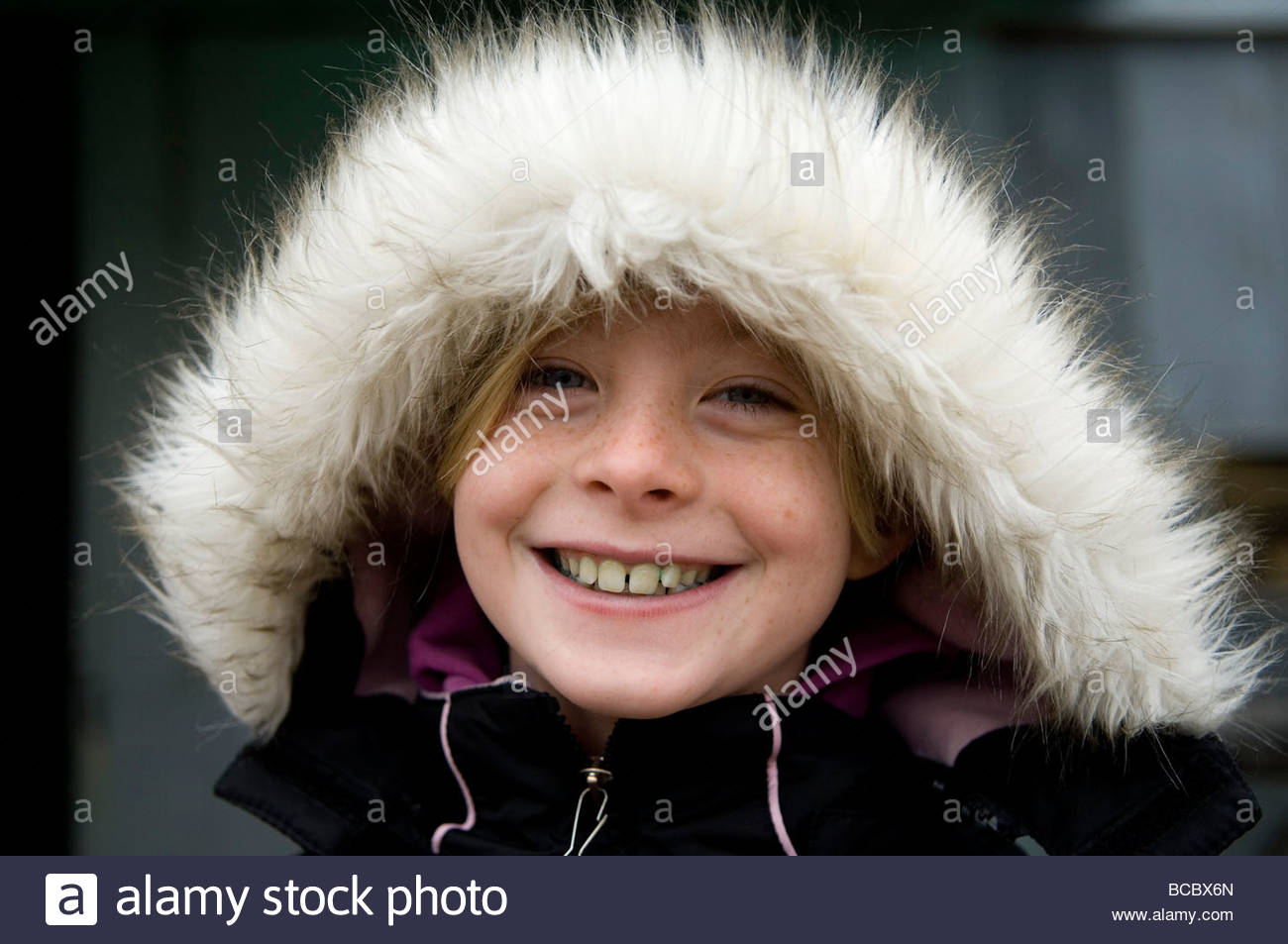 A young girl stands outside in a fur-trimmed coat. - Stock Image