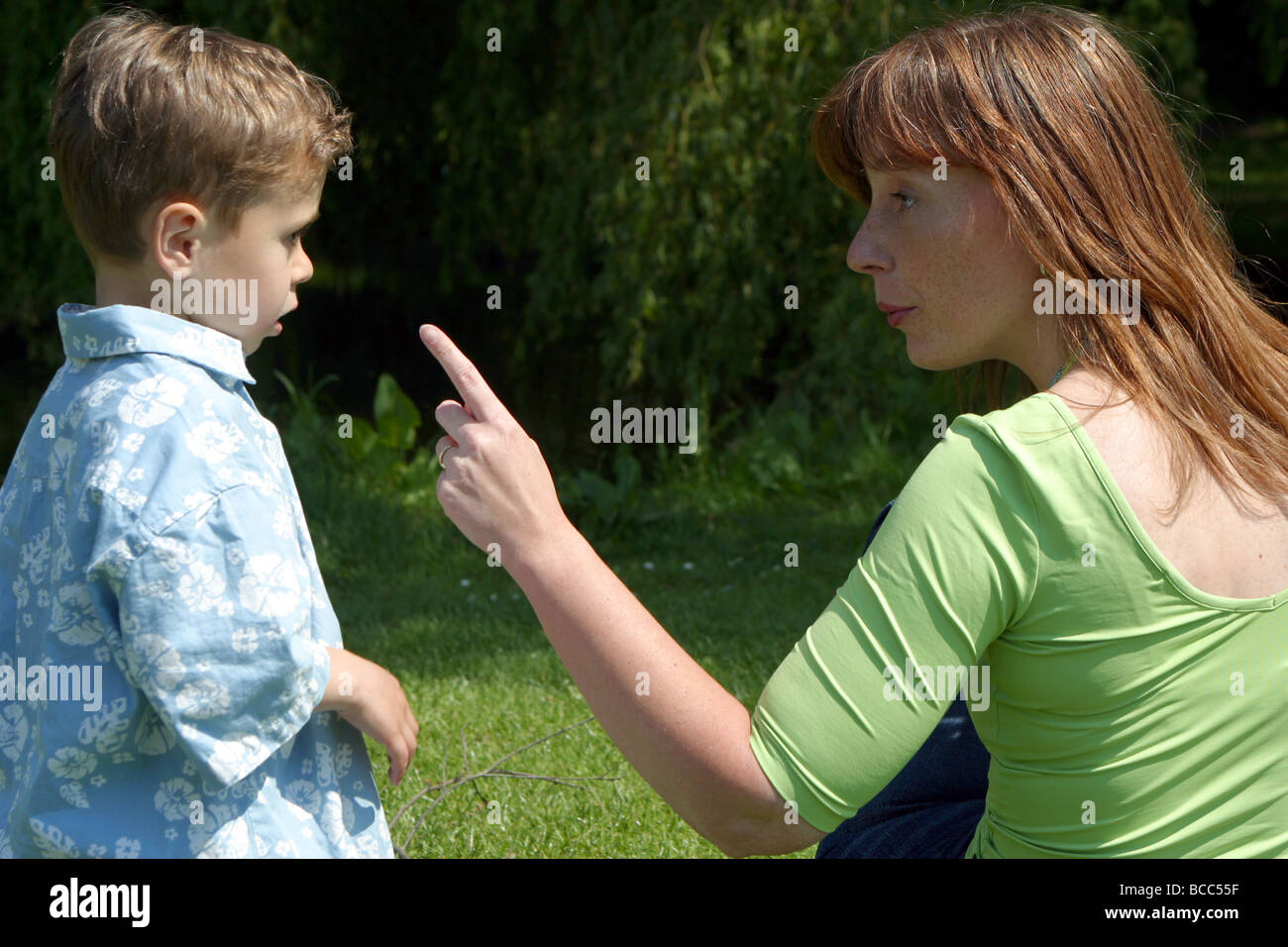 Rebellion little boy told off by his overprotective mother outside, she is warning and pointing at her toddler son Stock Photo