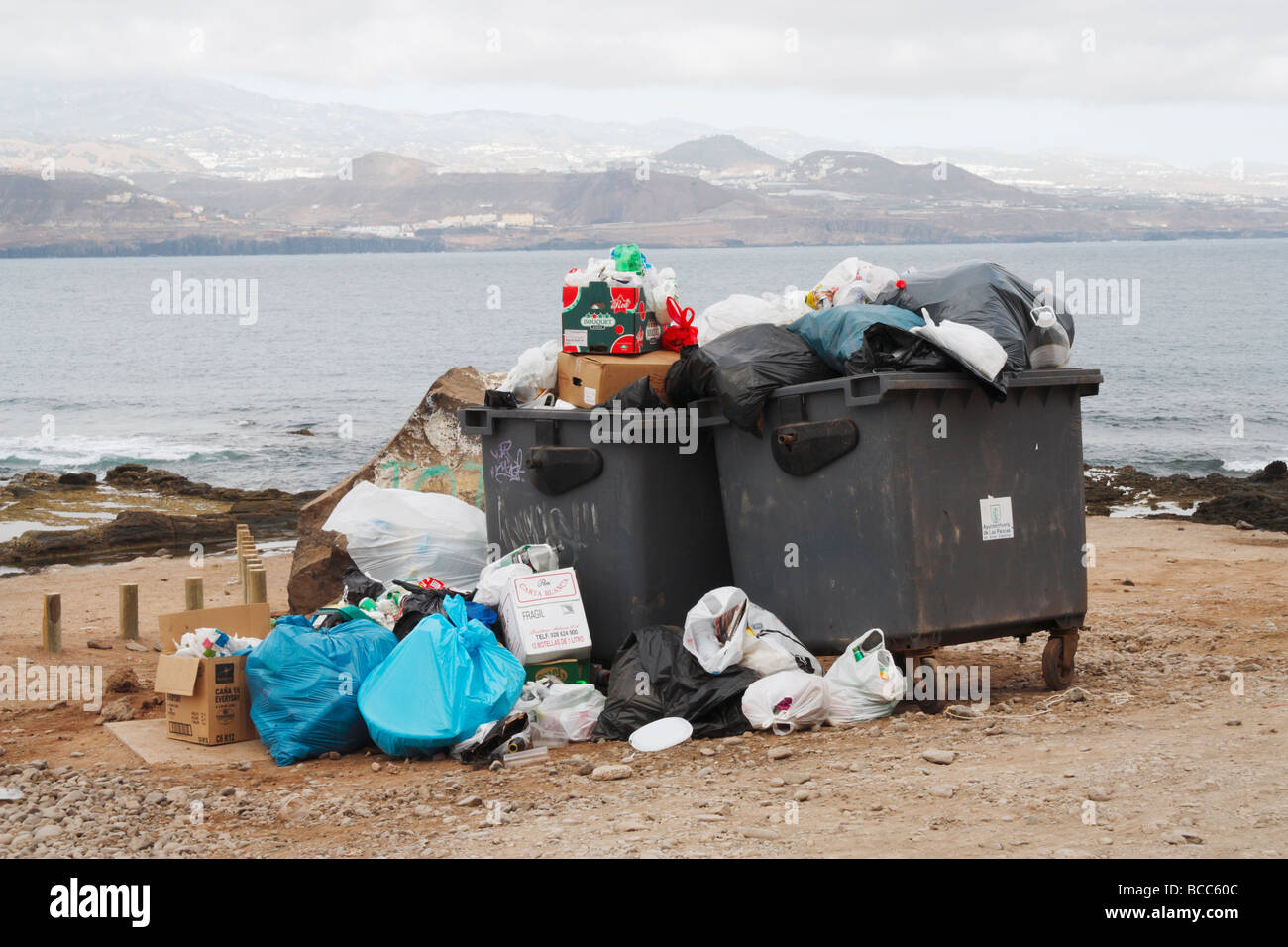 Piles of rubbish around rubbish containers after weekend near beach in Spain - Stock Image