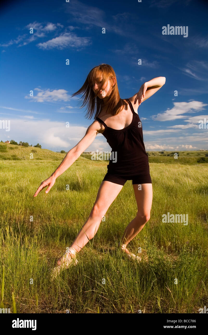 Young Ballerina posing in field - Stock Image