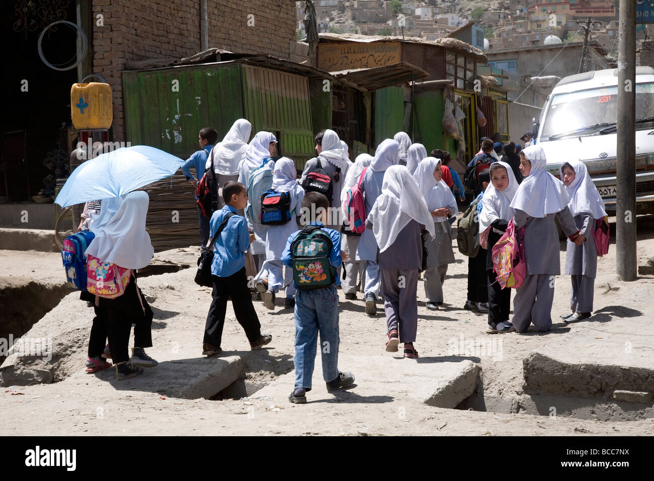 Schoolchildren--veiled girls and bareheaded boys--in a Kabul city street, Afghanistan - Stock Image