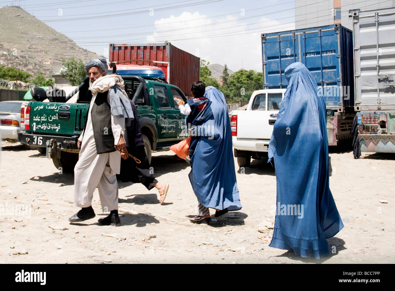 Crossing a Kabul street, a family including women in concealing burqas, risks the hazardous traffic - Stock Image