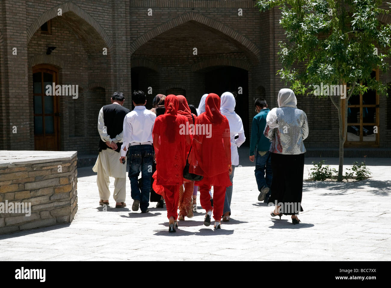 A prosperous Muslim family in Kabul leaving Babur's Gardens; bright red clothes indicate the daughters are unmarried - Stock Image