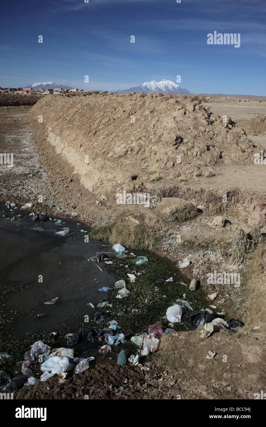 Rubbish in stream, Mt Illimani in background, Viacha, near El Alto, La Paz Department, Bolivia - Stock Image