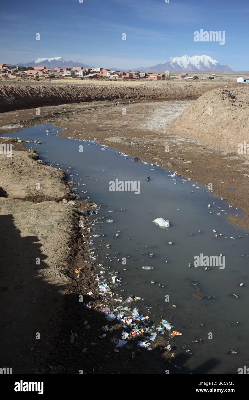 Rubbish in stream, Mts Mururata (L) and Illimani (R) in background, Viacha, near El Alto, La Paz Department, Bolivia - Stock Image