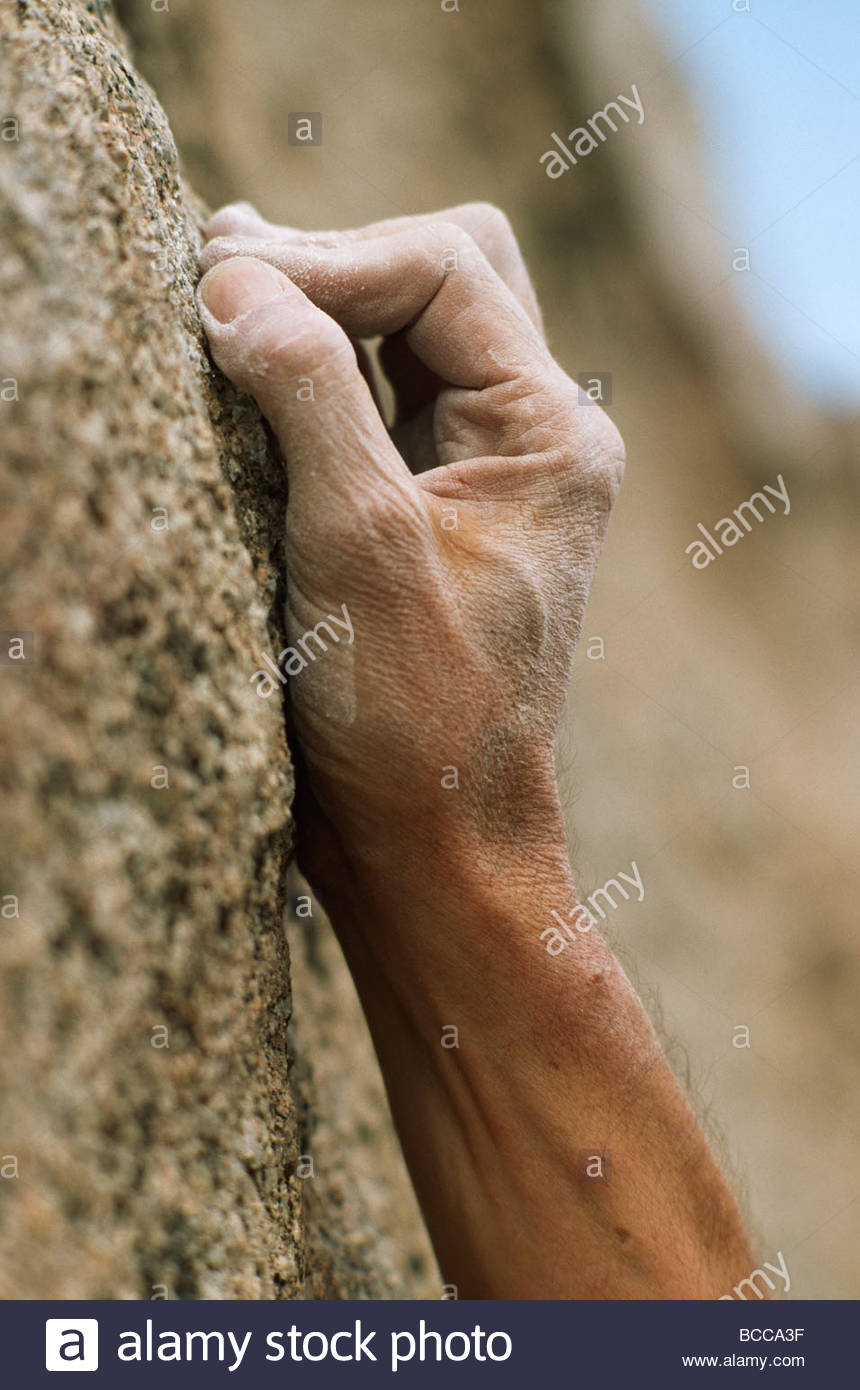 Rock climber grips a small granite hold. - Stock Image
