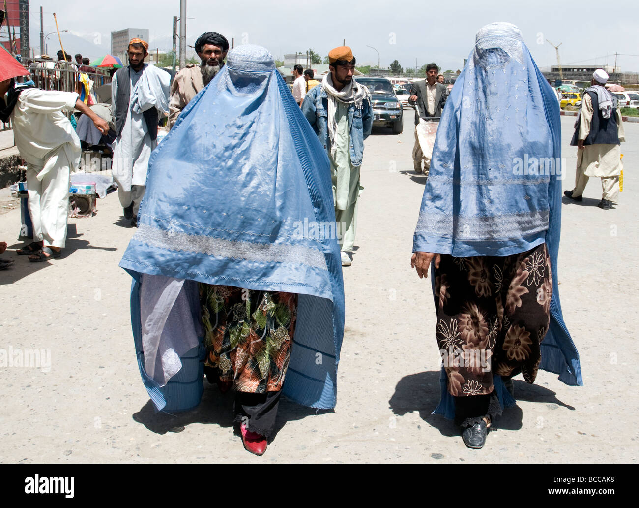 Two women in a Kabul street wear the customary blue burqas that hide their faces but partly reveal modest dress - Stock Image