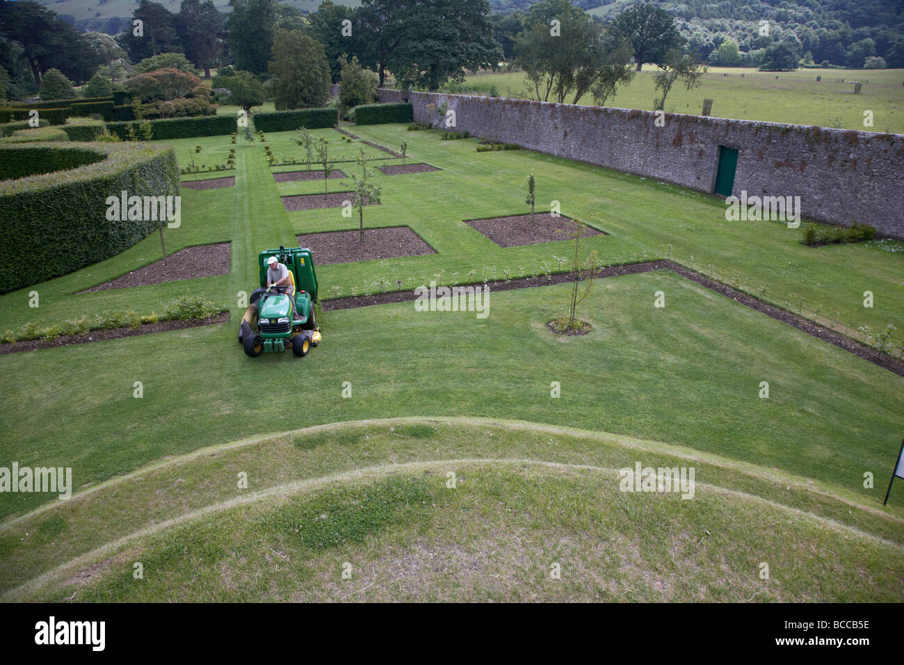 gardener mowing the lawn of the the walled garden at Glenarm castle county antrim northern ireland uk - Stock Image
