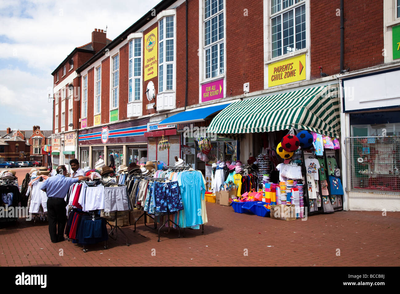 Street trader selling clothes outside shop on sea front Barry island Wales UK - Stock Image