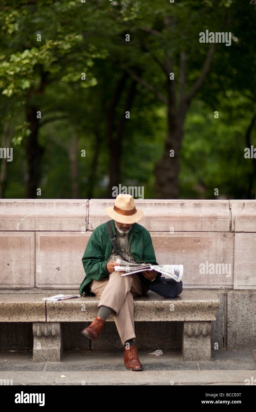 Black man sits on a stone bench by a park and reads the newspaper in New York USA May 2009 - Stock Image