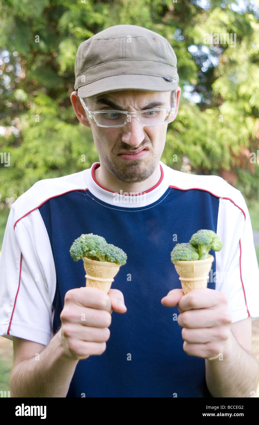 Young man frowning down at ice-cream cones filled with broccoli - Stock Image