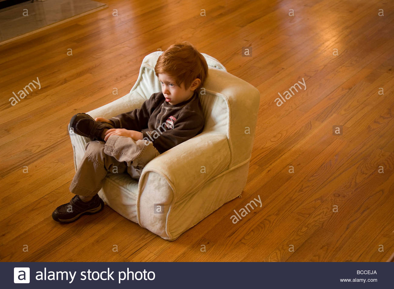 A 3 Year Old Boy Watches Tv In His Child Size Armchair Stock Photo