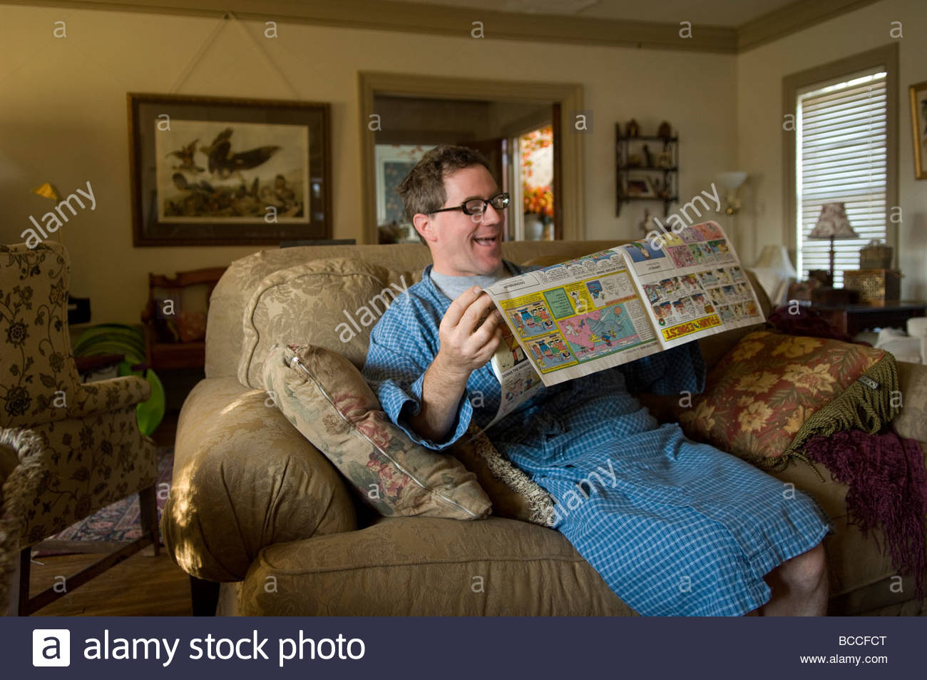 A man reads the comics from the morning newspaper. - Stock Image