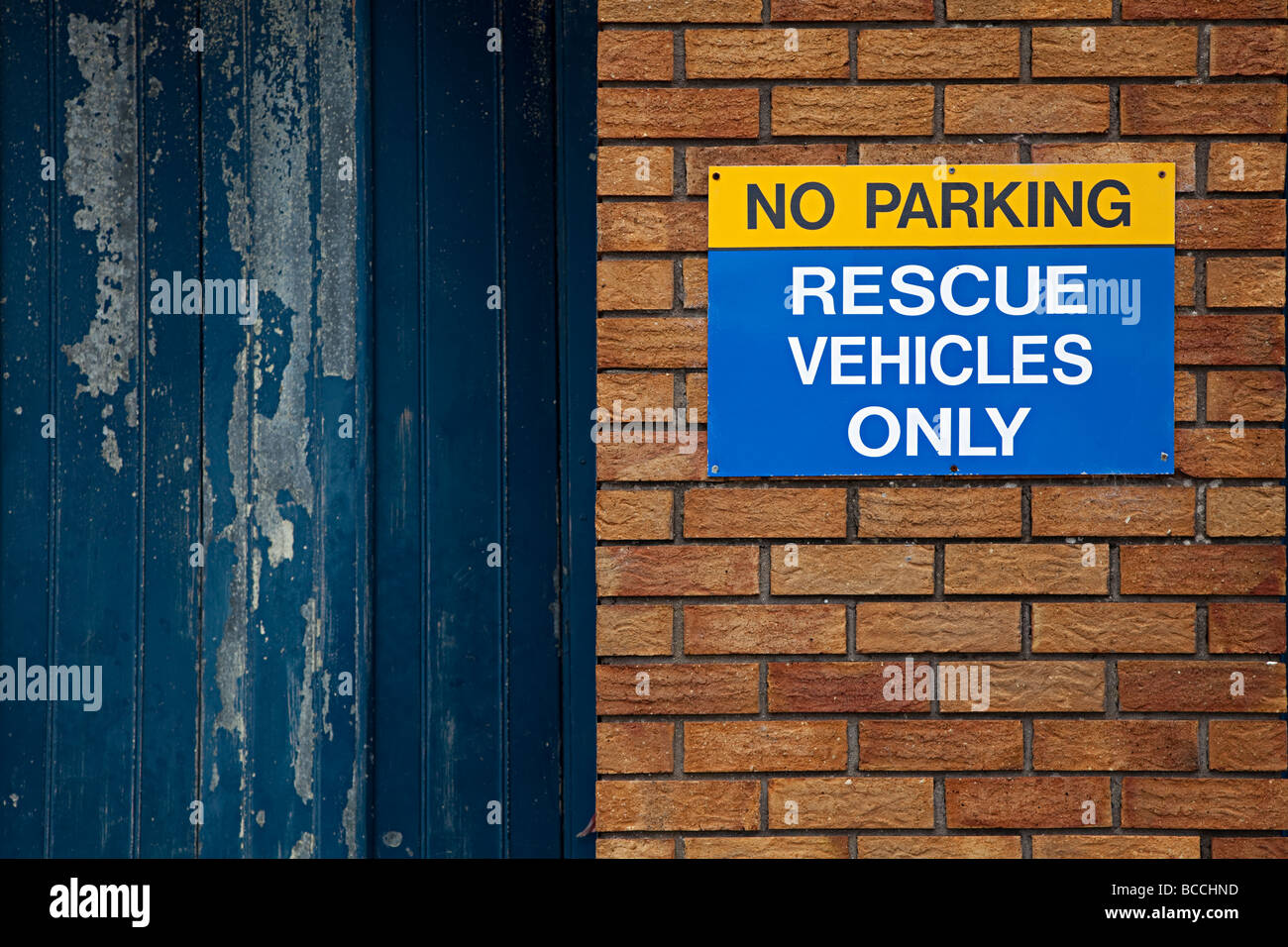 No parking rescue vehicles only sign on brick wall next to faded paint garage door Barry Wales UK - Stock Image