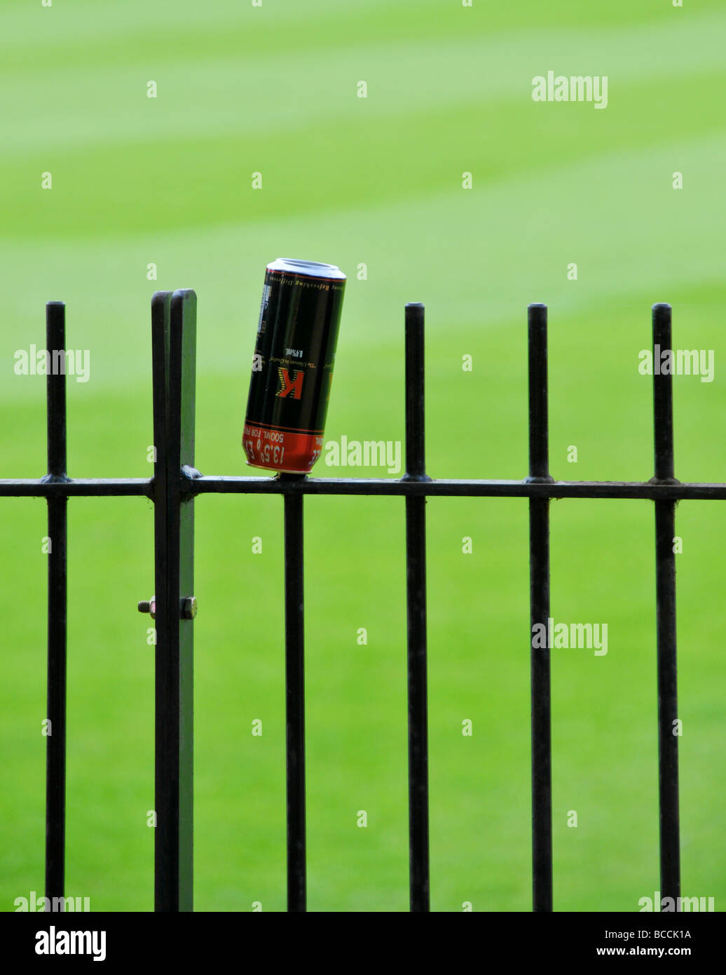 Discard Beer Can on fence - Stock Image