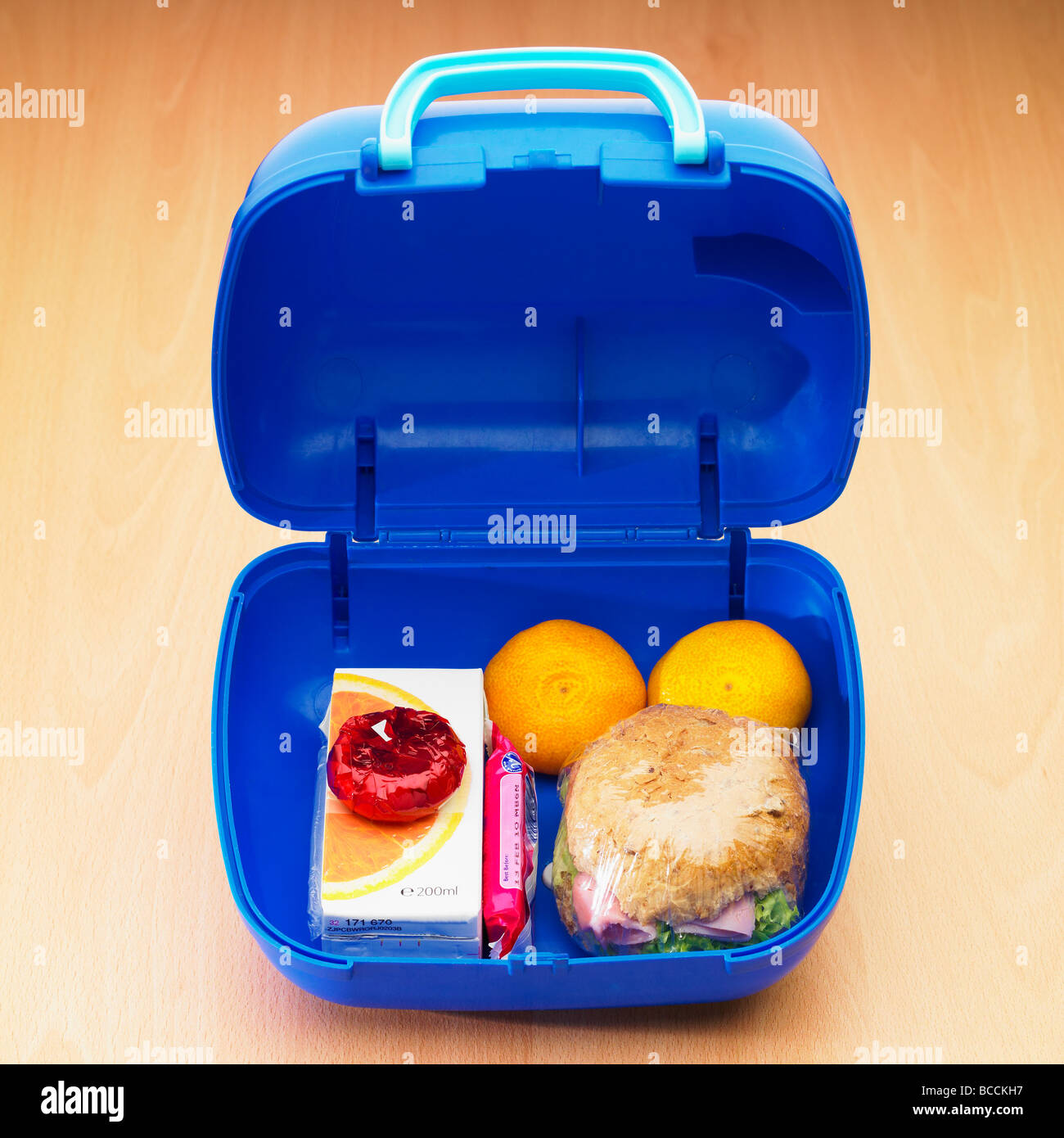 Healthy childrens school lunch box with wholemeal roll, satsumas, mini light cheese, orange juice and biscuit. - Stock Image