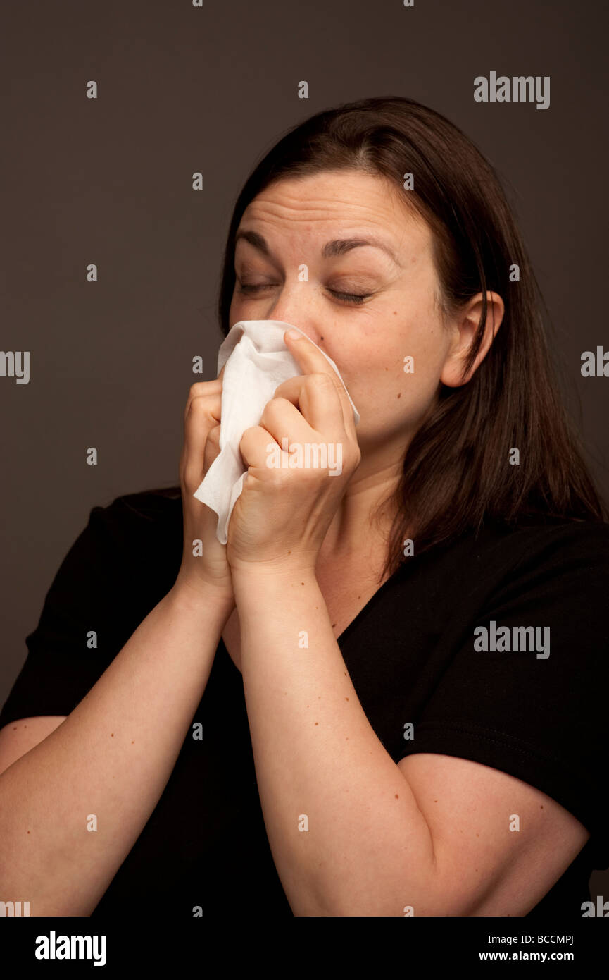 A Woman suffering from cold flu hay fever influenza ill sick sneezing into a paper handkerchief - Stock Image