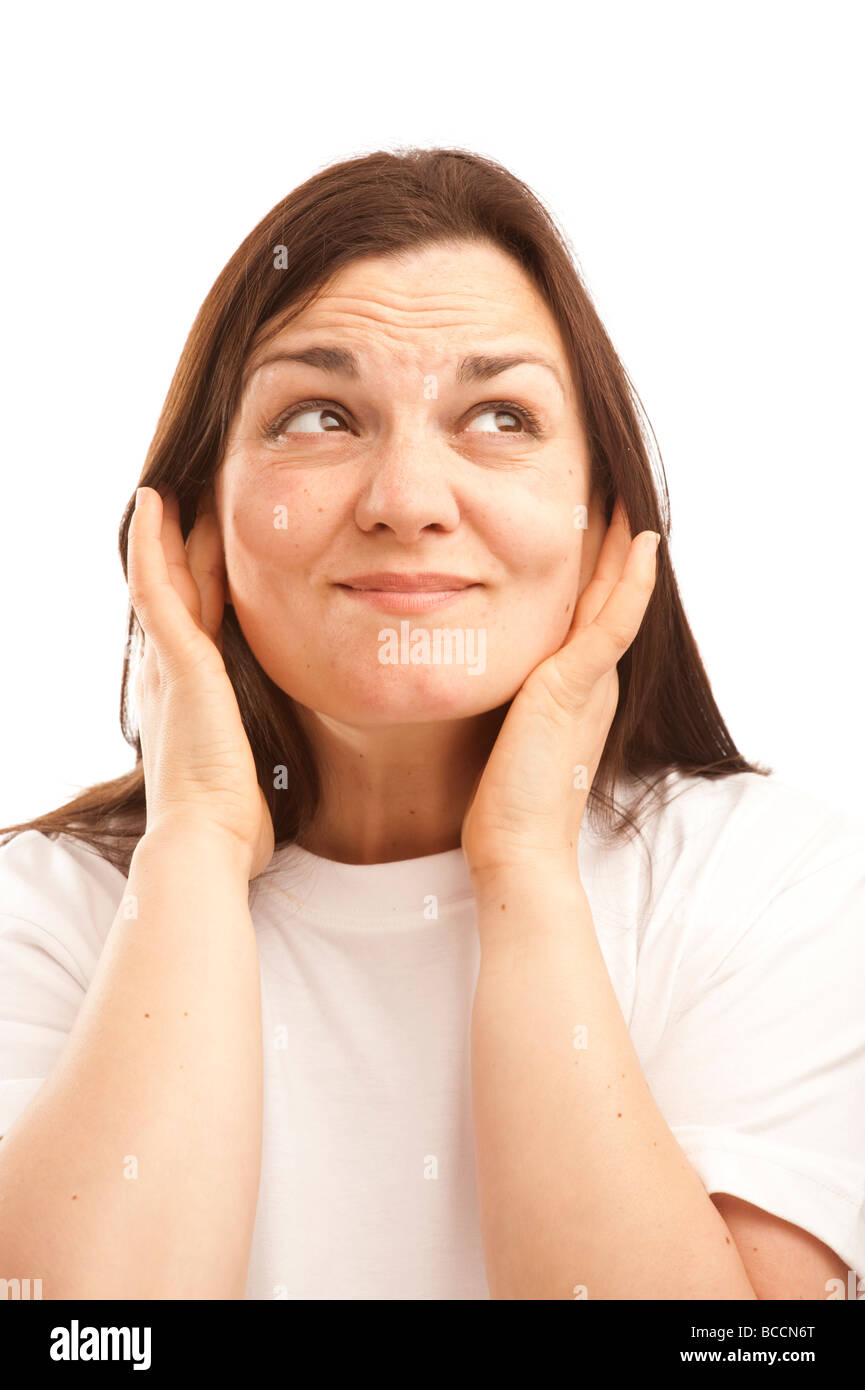 a young woman with her fingers in her ears to keep out loud deafening noise - Stock Image