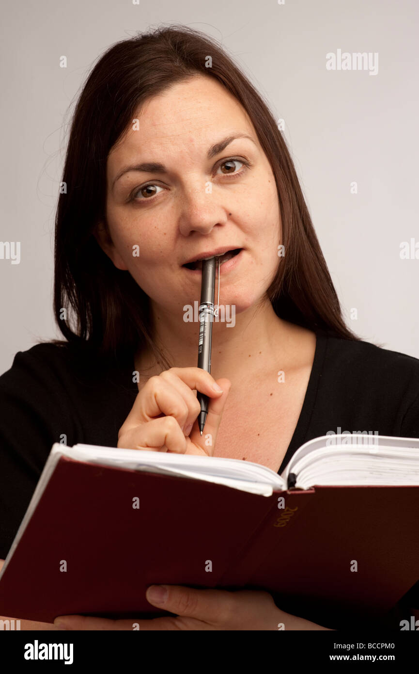 A young woman 20-30 years old writing in her daily diary journal notebook - Stock Image