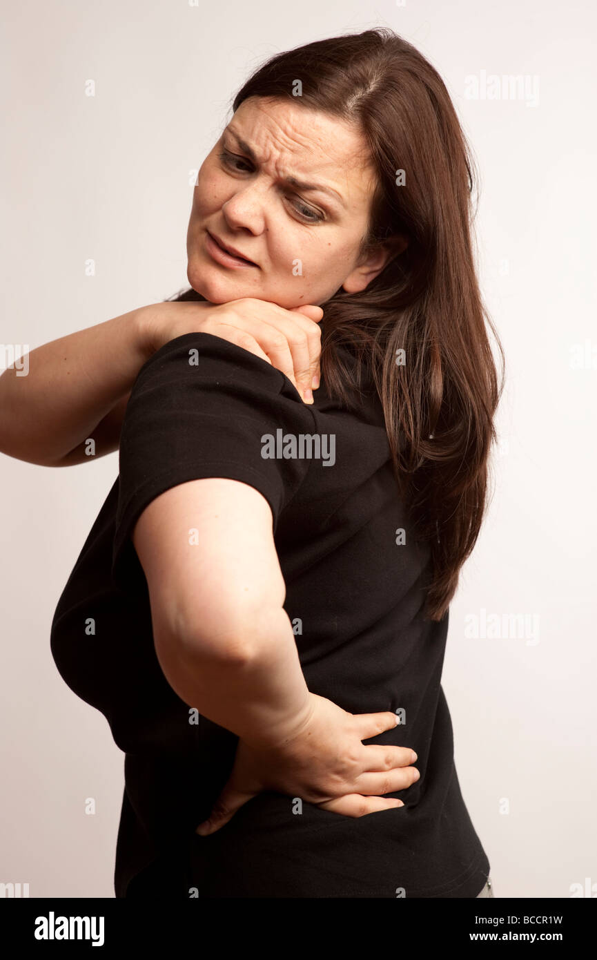 A woman suffering from back ache or shoulder pain - Stock Image