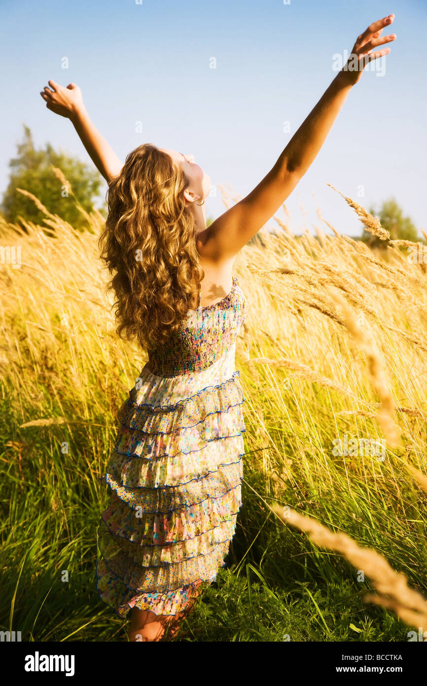 Young woman stretching up in a summer field - Stock Image