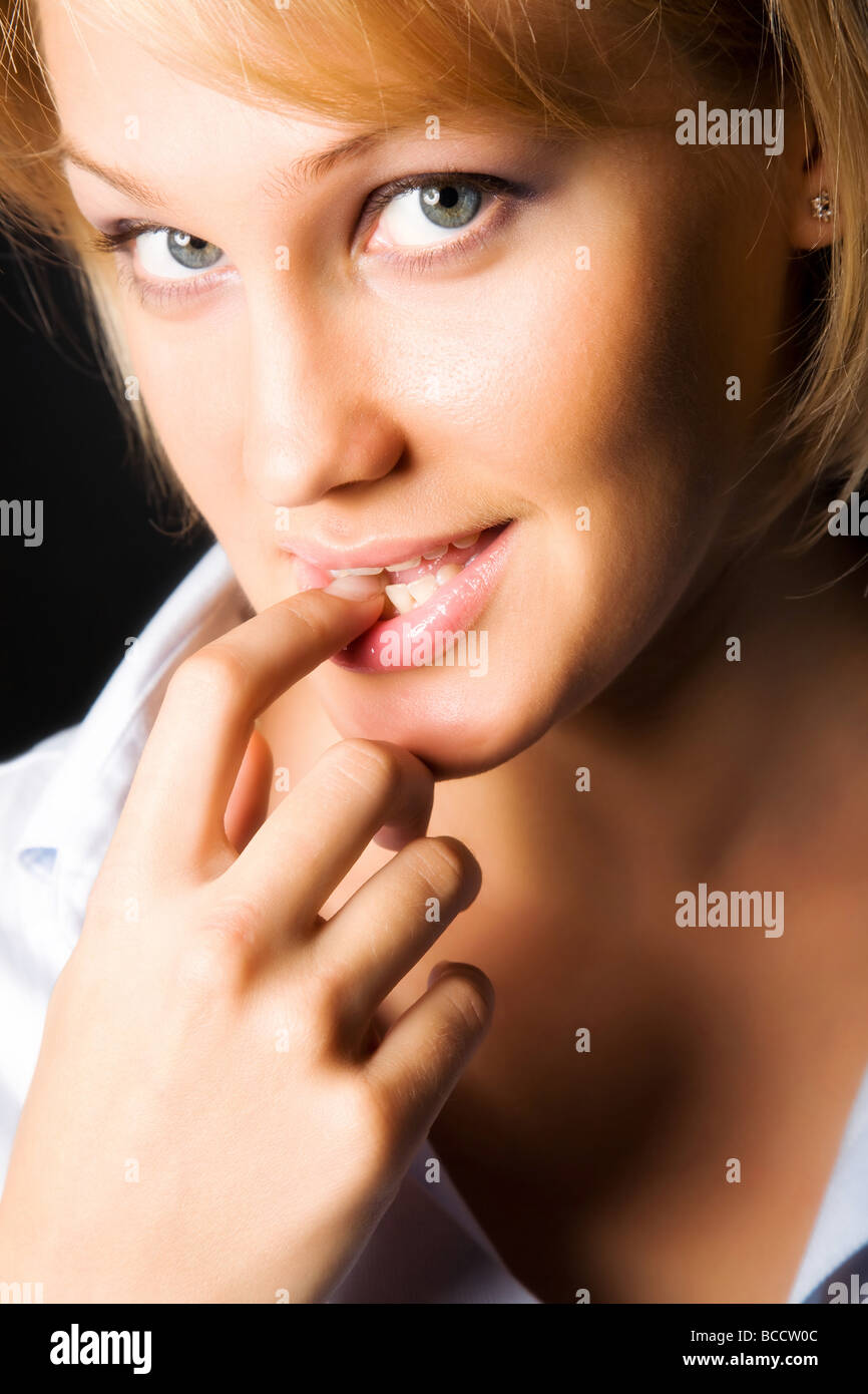 Young skittish woman On dark background - Stock Image