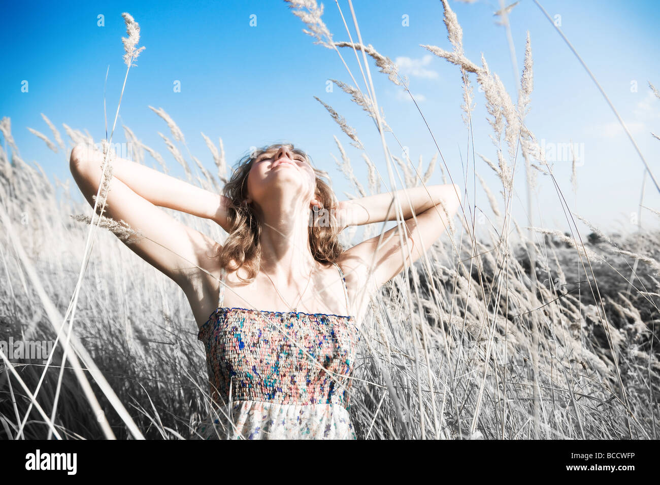 Young woman on a summer field Infra red photo effect - Stock Image