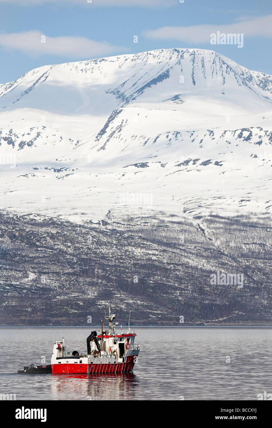 Norwegian red fishing trawler and cargo vessel at Storfjord Skibotn Norway - Stock Image