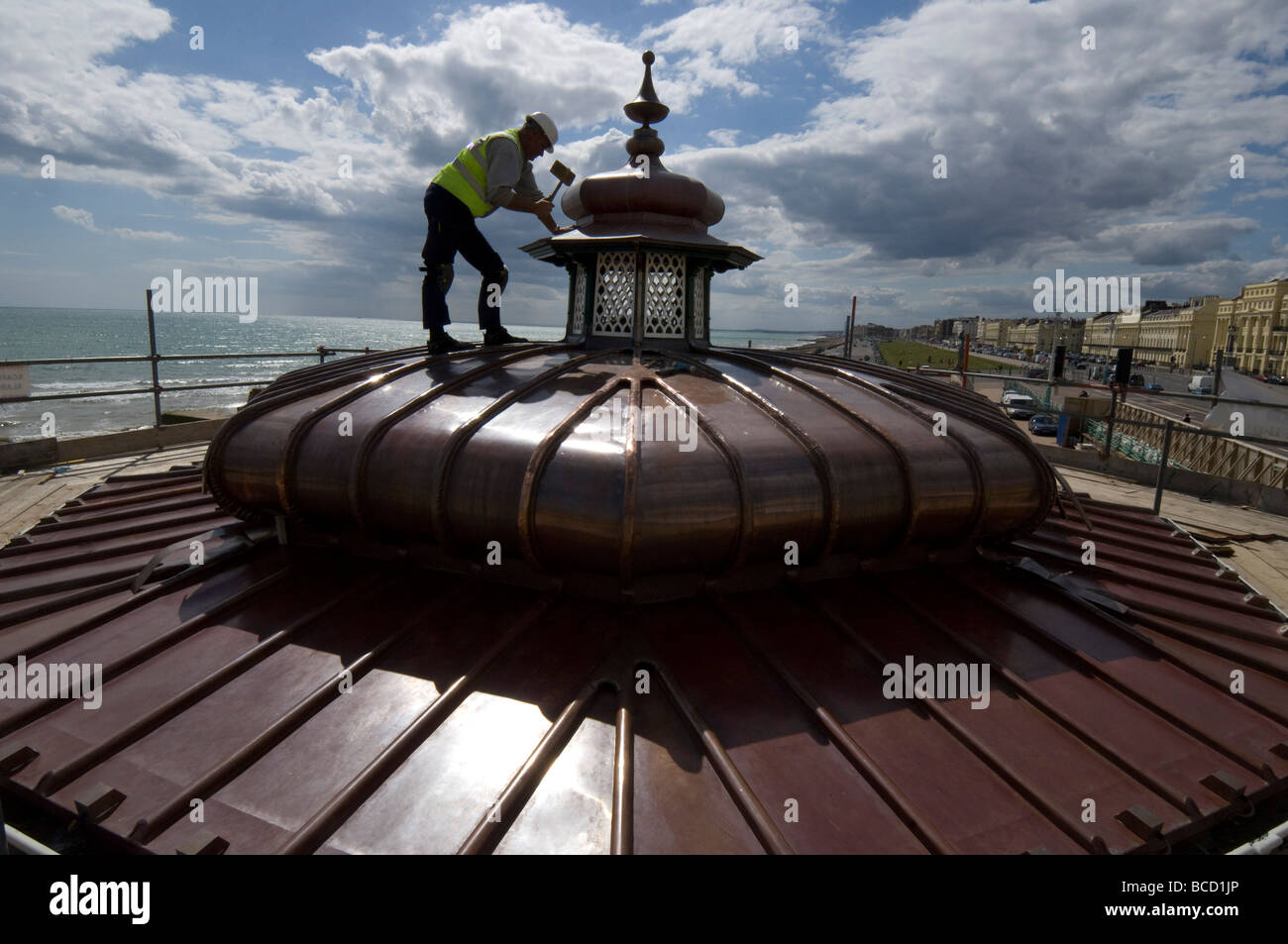 A workman hammering a new copper roof onto a Victorian bandstand on Brighton and Hove seafront - Stock Image