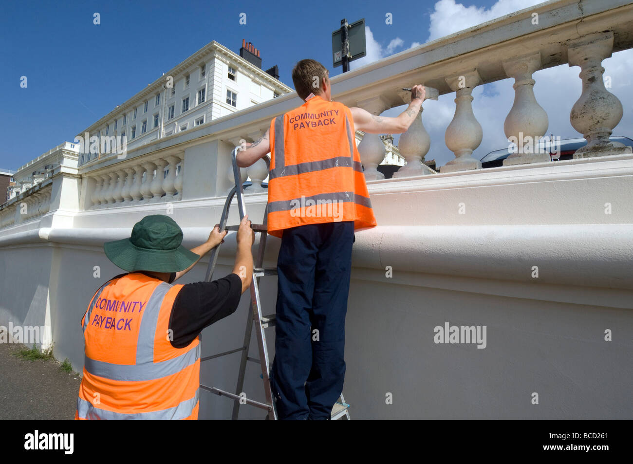 Convicted criminals doing painting and decorating in orange tabards with community payback slogan on the back - Stock Image