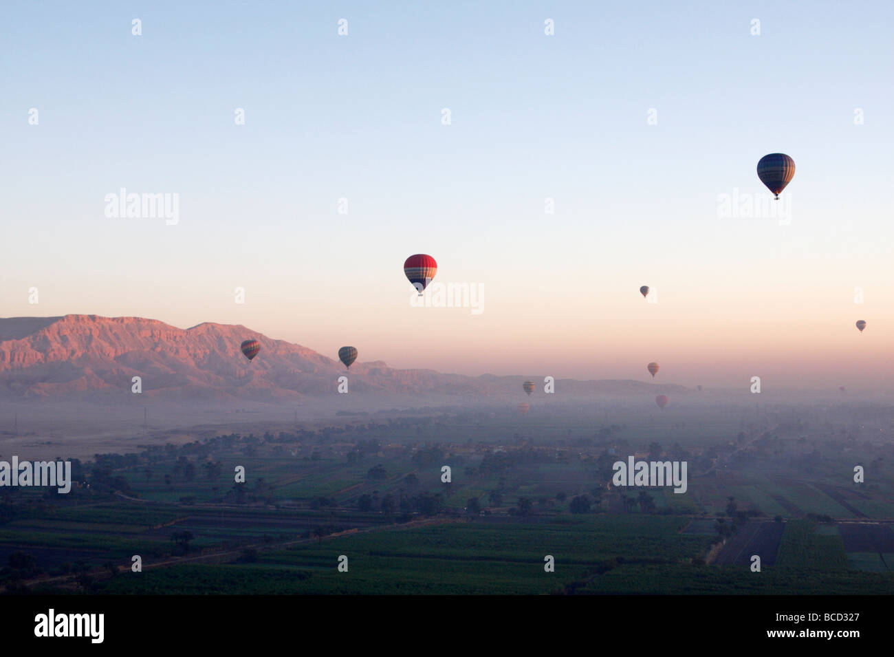 """[Hot air balloons] flying high over """"West Bank"""" at sunrise, Luxor, Egypt Stock Photo"""