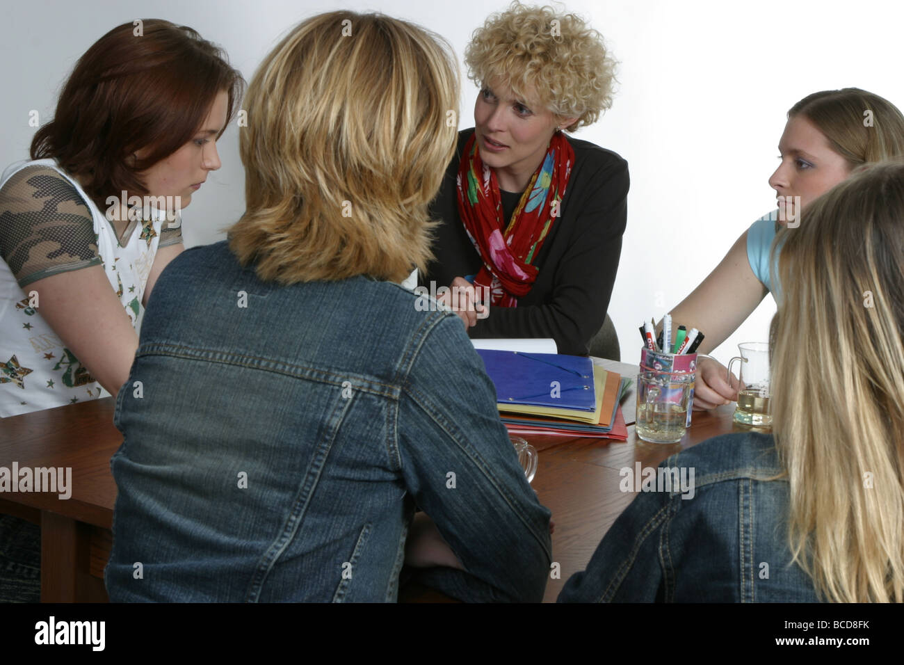 Youth worker or teacher talking with problem teenagers. The  adult woman is having a serious conversation with the - Stock Image
