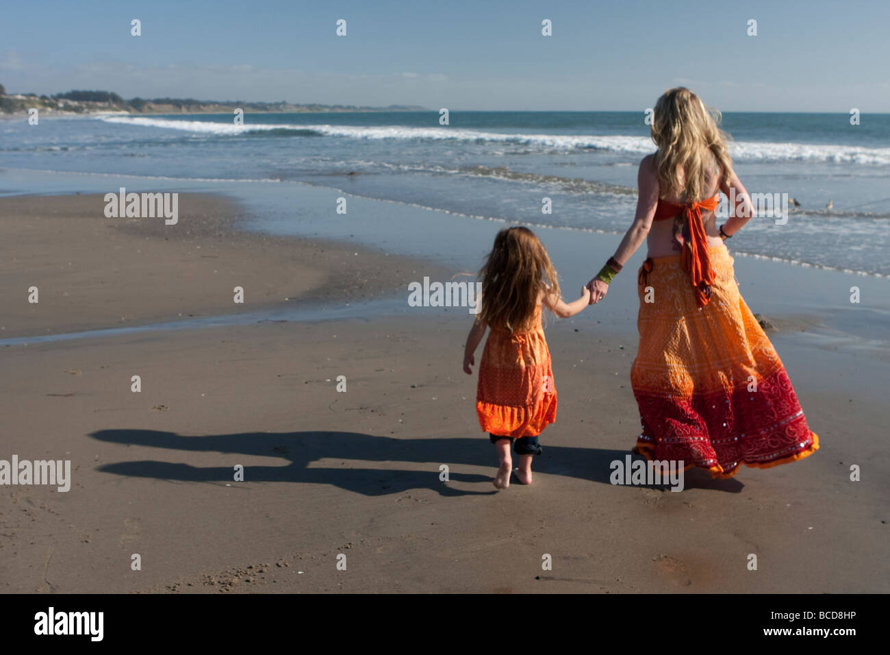 Woman and girl on a California beach, walking away from camera.  Seacliff State Beach, near the 'cement ship.' - Stock Image
