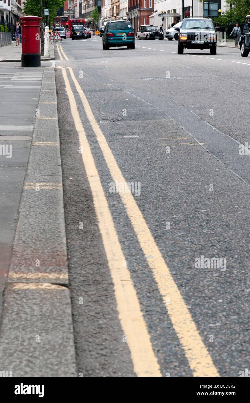 Double yellow line on street London England UK - Stock Image